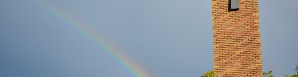 picture of church pillar, st lukes cross and rainbow across sky