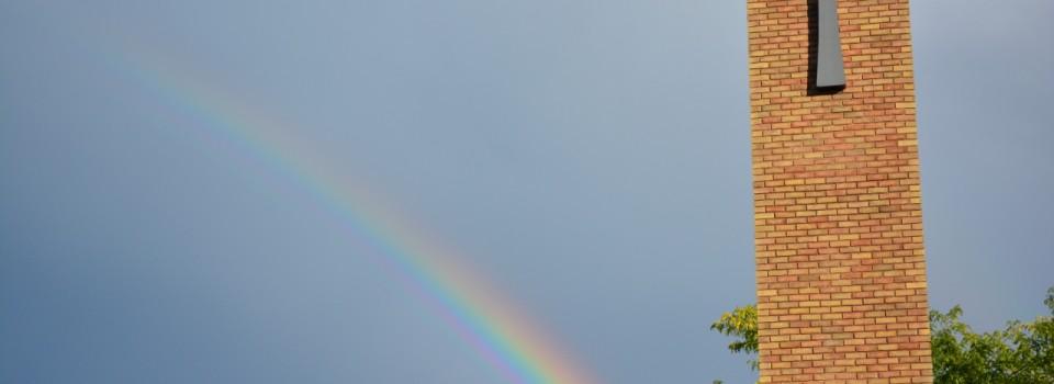 picture of church pillar, st lukes cross and rainbow across sky
