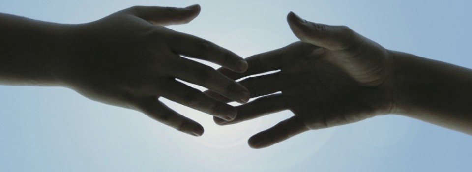 Two hands touching fingertips to show that we remain connected