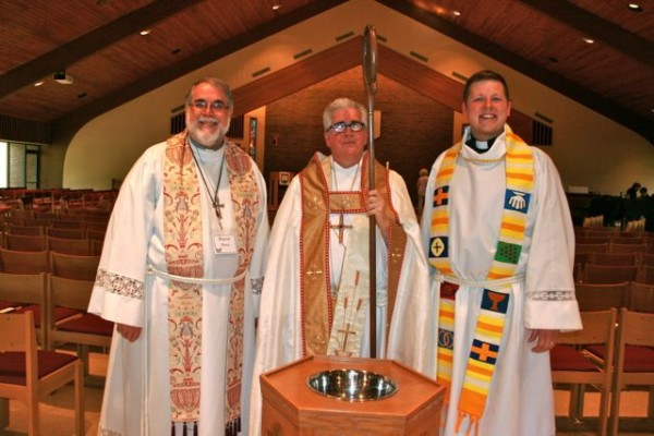 image of bishop Saterlee, pastor Blank and pastor Werner around baptismal font
