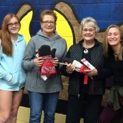 image of chili cook off winners holding prize of oven mitts and cooking spoons