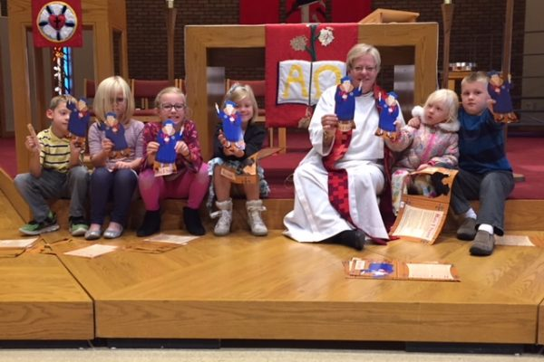 image of Pastor and children holding paper Martin Luther dolls