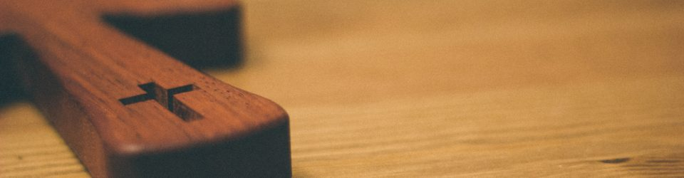 image of a small wooden cross lying on a wooden table