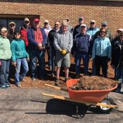 group of people standing in front of church with a wheelbarrow full of mulch