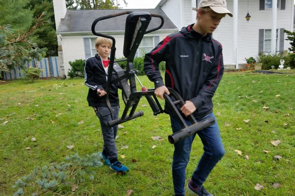 Teen boys carrying exercise equipment