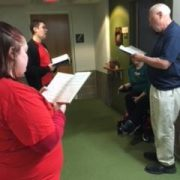 Adults singing in a hallway