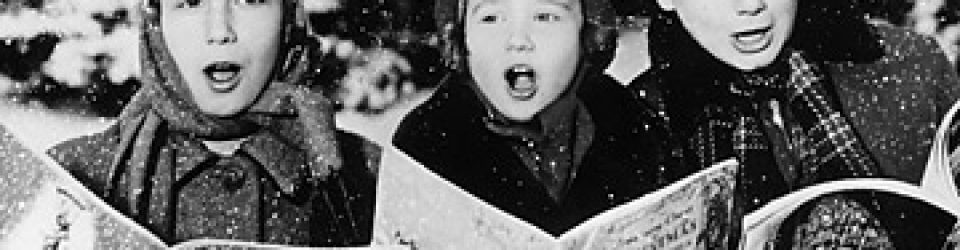 three young children singing christmas carols