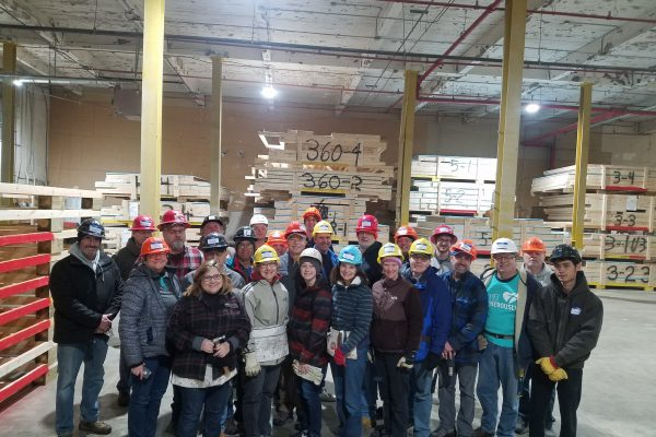 Group of people dressed in work clothes in a warehouse
