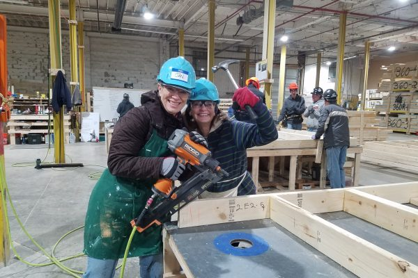 Jan and Sue in work clothes and hard hats, smiling and holding a hammer and nail gun
