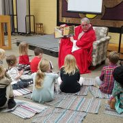 children sitting on the floor listening to a story read by Pastor Dave dressed as St. Nicholas