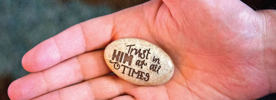 """rock etched with """"Trust in him at all times"""" resting in open palm"""