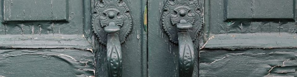 image of double doors with ornate handles and locks. The doors are weathered and aged, and the door handles and locks are painted over and the paint on the doors is peeling
